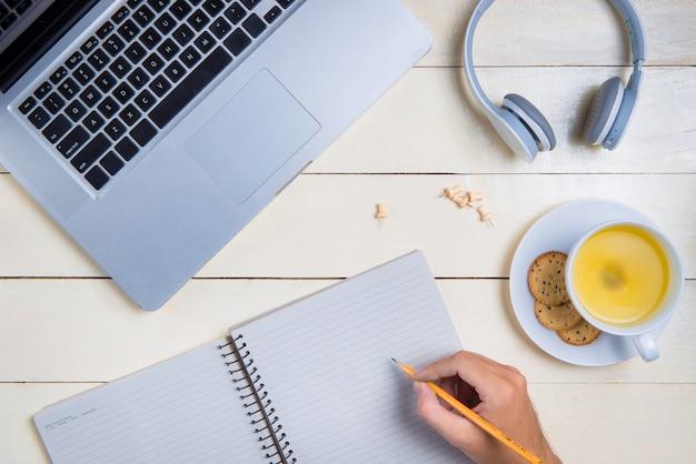 Женщина почерков с карандашом на чистый лист бумаги ноутбук с портативным компьютером на офисном столе, вид сверху
