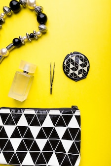 Woman handbag with makeup and accessories on yellow surface,