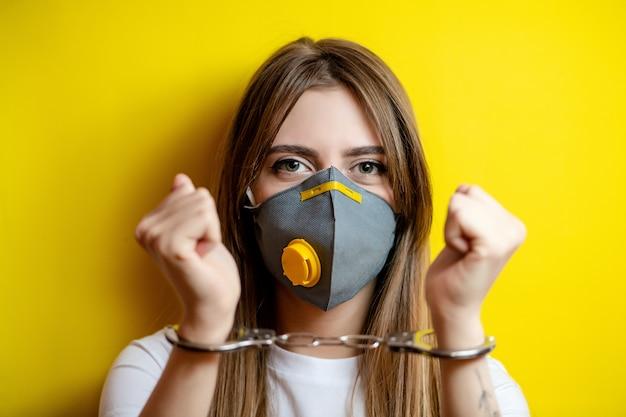 Woman in handcuffs wearing respirator mask