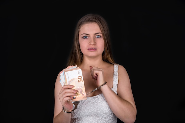 Woman in handcuffs with euro banknotes isolated on black