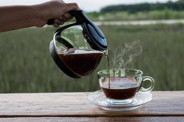 Женщина держит кофейник и падает в стакан на деревянном столе