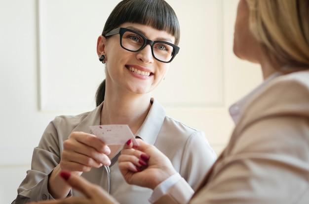 会議で名刺を渡す女性