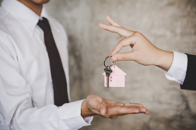 Woman handing over the house keys to a new home inside empty gray colored room.