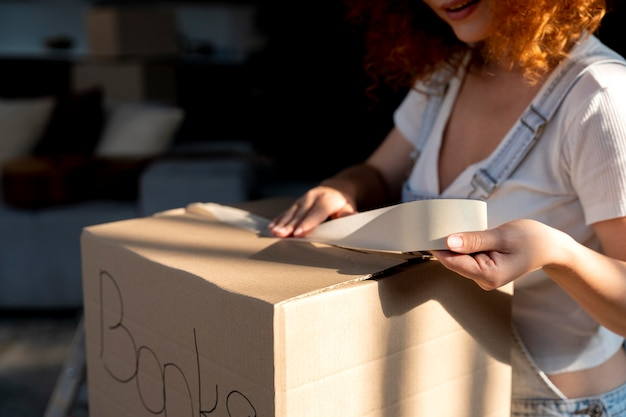 Woman handling belongings in cardboard boxes for moving in new house