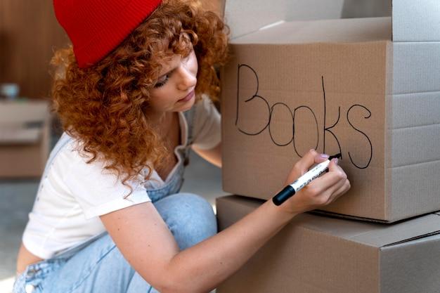 新しい家に引っ越すための段ボール箱で持ち物を扱う女性