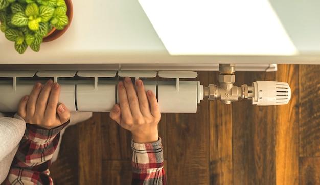 Руки женщины и радиатор отопления в квартире с фоном современного интерьера