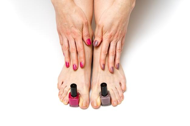 Женщина руки и ноги держит лак для ногтей