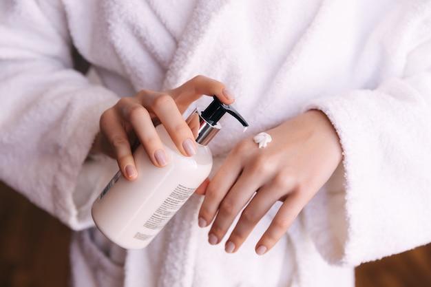 Руки женщины, применяя увлажняющий крем к ее коже