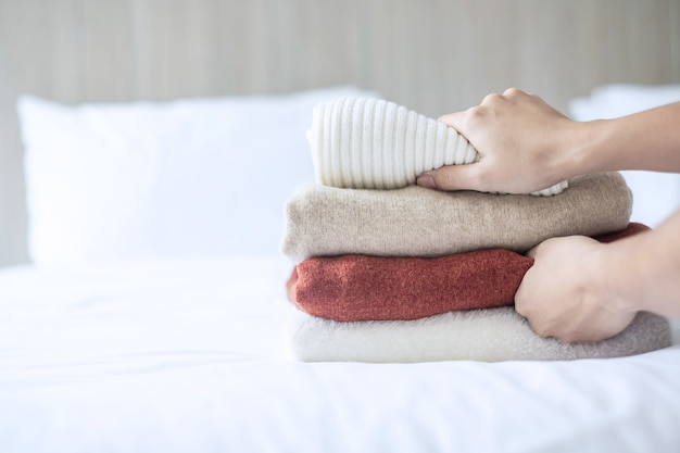 女性の手は、高級ホテルやリゾート、自宅のベッドにベージュのウールのセーターを配置します。リラックス、秋または冬の服、ランドリー、休暇の概念