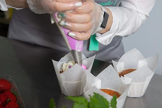 여자 손 요리사 과자 가방을 들고 컵 케이크에 크림을 짜내.