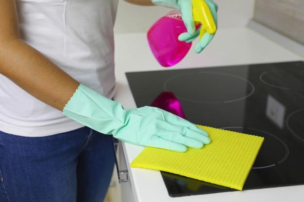 Руки женщины чистят современную черную индукционную плиту тряпкой и спреем.