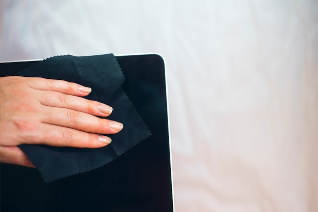 Woman hands cleaning laptop