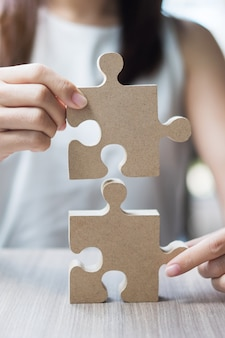 Woman hands connecting couple puzzle over table, businesswoman holding wood jigsaw inside office.