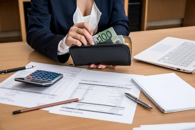 여자 손 문서 홈 예산 lapptop 펜 및 계산기와 유로 돈을 계산