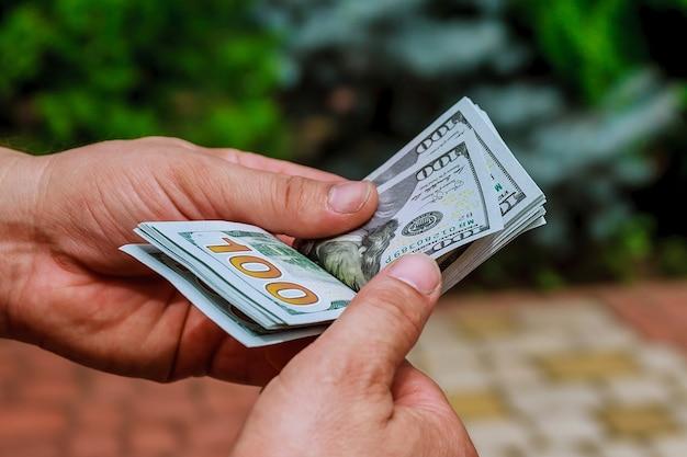 Руки женщины, считая банкноты доллара сша. считать или потратить деньги.