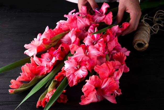 Woman hands create a bouquet of flowers of gladiolus