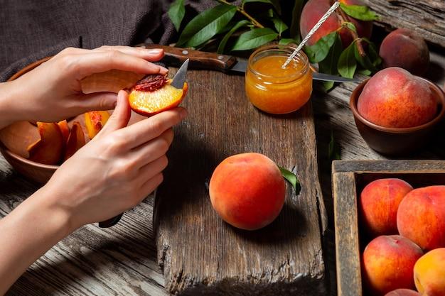 여자 손은 소박한 커팅 보드에 잼, 디저트, 주스를 위한 조리법을 만들기 위해 복숭아를 자릅니다. 복숭아는 잎이 있는 과일 전체, 복숭아는 반으로, 복숭아 조각은 나무 테이블에 있습니다. 어두운 분위기.