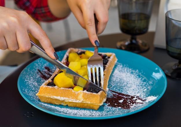 Woman hands cutting belgium waffles