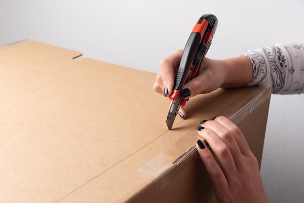 Женщина руками режет картонную коробку по отмеченной линии, нарисованной на коробке с местом для копирования, для добавления объяснения учебника или руководства, как это сделать.