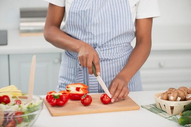Руки женщины режут вкусные помидоры