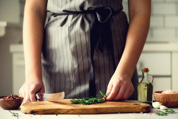 Woman hands cutting fresh green rosemary on wood chopping board in white kitchen