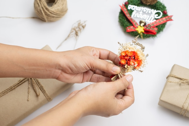 Woman hands decorating christmas craft handmade presents with dried flower