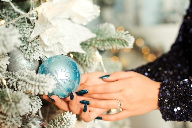 Руки женщины украшают елку шариками