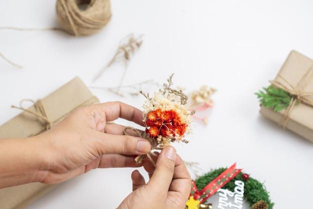 Женские руки украшают подарки сухофруктами и сосновыми листьями для рождественской подарочной коробки