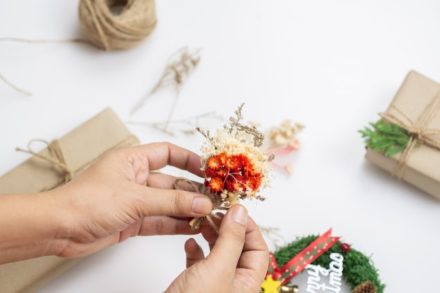 Woman hands decorating presents with dried flower and pine leaves for christmas gift box