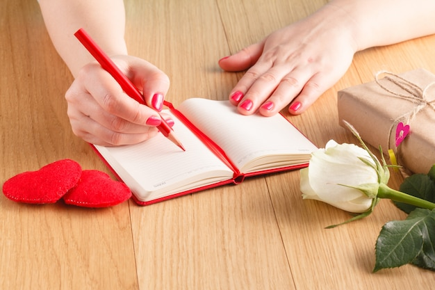 Woman hands drawing or writing, gift box, red hearts on wooden table
