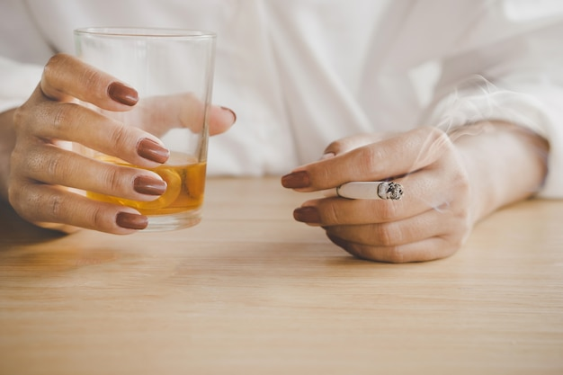 Woman hands drinking alcohol and smoking cigarette