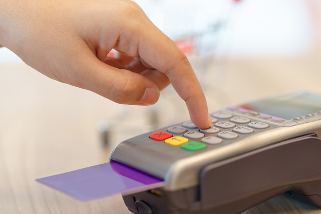 Woman hands entering code for paying via credit card - shopping concept.