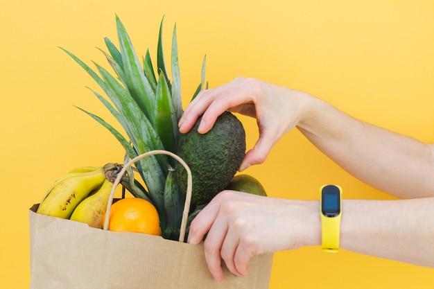 노란색 배경에 여러 과일로 종이 가방을 채우는 여자 손.