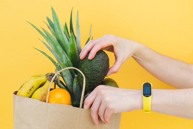 Woman hands filling paper bag with assorted fruit on yellow background.