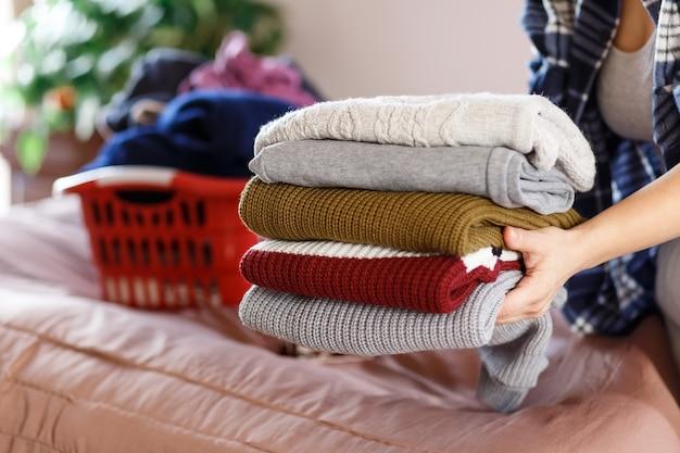 Женщина руки складывает одежду, вязаные уютные свитера в спальне, собирает после стирки. концепция домработницы