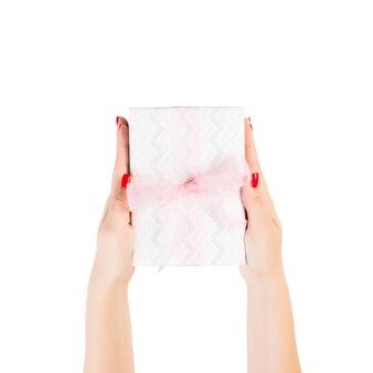 여자 손은 분홍색 리본이 달린 색종이에 포장된 크리스마스 또는 기타 휴일 수제 선물을 제공합니다. 흰색 배경, 상위 뷰를 격리합니다. 추수 감사절 선물 상자 개념입니다.