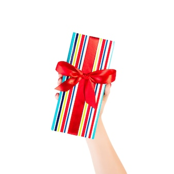 여자 손에 빨간 리본이 달린 색종이에 포장 된 크리스마스 또는 다른 휴일 수제 선물 제공