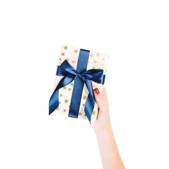 여자 손은 블루 리본이 달린 금색 종이에 포장 된 크리스마스 또는 다른 휴일 수제 선물을 제공합니다.
