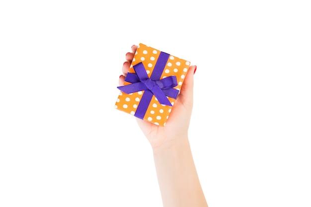 여자 손은 보라색 리본이 달린 주황색 종이에 포장된 크리스마스 또는 기타 휴일 수제 선물을 제공합니다. 흰색 배경, 상위 뷰를 격리합니다. 추수 감사절 선물 상자 개념입니다.