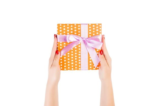 여자 손은 보라색 리본이 달린 주황색 종이에 포장 된 크리스마스 또는 다른 휴일 수제 선물을 제공합니다.