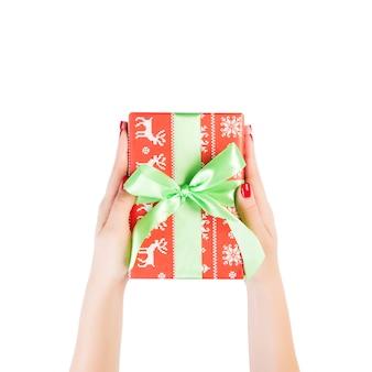 Руки женщины дарят обернутый подарок на рождество или другой праздник ручной работы в красной бумаге с зеленой лентой. изолированные на белом фоне, вид сверху. концепция подарочной коробки благодарения.
