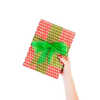 여자 손은 그린 리본이 달린 빨간 종이에 포장된 크리스마스 또는 기타 휴일 수제 선물을 제공합니다. 흰색 배경, 상위 뷰를 격리합니다. 추수 감사절 선물 상자 개념입니다.