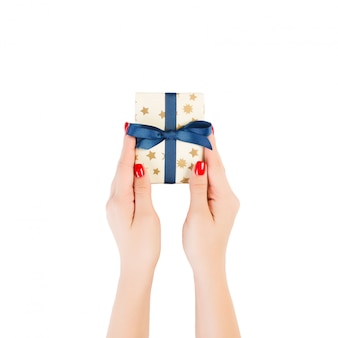 Woman hands give wrapped christmas or other holiday handmade present in gold paper with blue ribbon. isolated on white