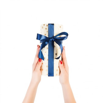 Woman hands give wrapped christmas or other holiday handmade present in gold paper with blue ribbon