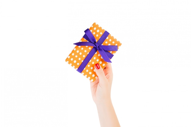 Woman hands give wrapped christmas or other holiday handmade present in orange paper with purple ribbon.