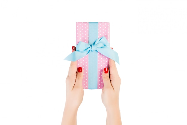 Woman hands give wrapped christmas or other holiday handmade present in pink paper with blue ribbon