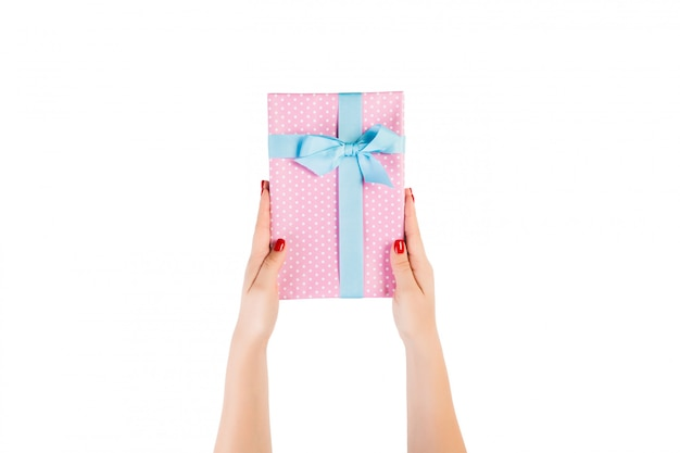 Woman hands give wrapped christmas or other holiday handmade present in pink paper with blue ribbon.