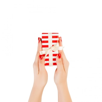 Woman hands give wrapped christmas or other holiday handmade present in red paper with gold ribbon. isolated on white