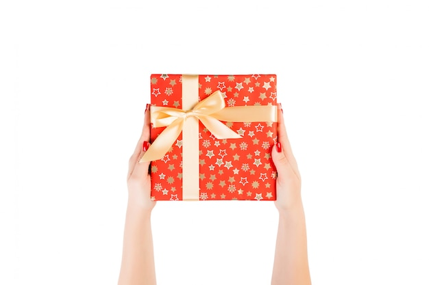 Woman hands give wrapped christmas or other holiday handmade present in red paper with gold ribbon