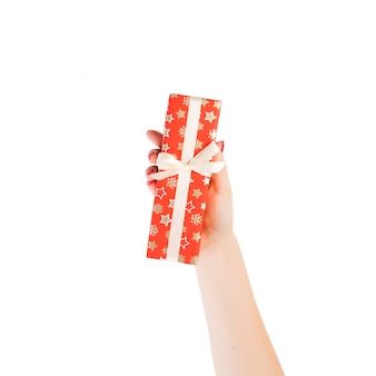 Woman hands give wrapped christmas or other holiday handmade present in red paper with gold ribbon.